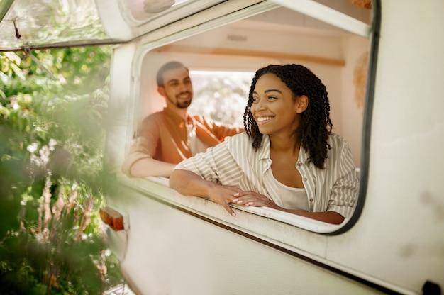 Man en vrouw kijken uit het raam van de camper en kamperen in een aanhangwagen. man en vrouw reizen met een busje, romantische vakanties op de camper, kampeerders maken zich vrij in de camper