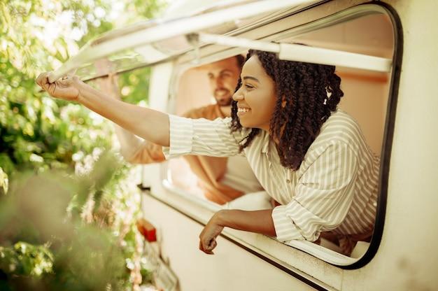 Man en vrouw kijken uit het raam van de camper en kamperen in een aanhangwagen. man en vrouw reizen met een busje, vakanties met de camper, kampeerders vrije tijd in de camper