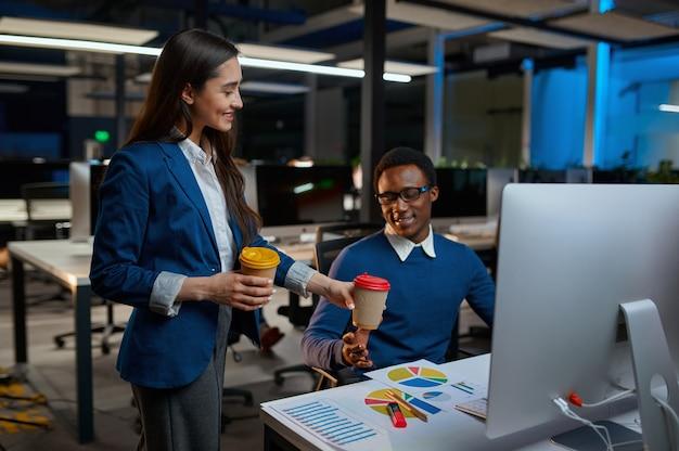 Man en vrouw kijkt op het scherm, kantoorlevensstijl. mannelijke en vrouwelijke personen praten op laptop, donker interieur, moderne werkplek