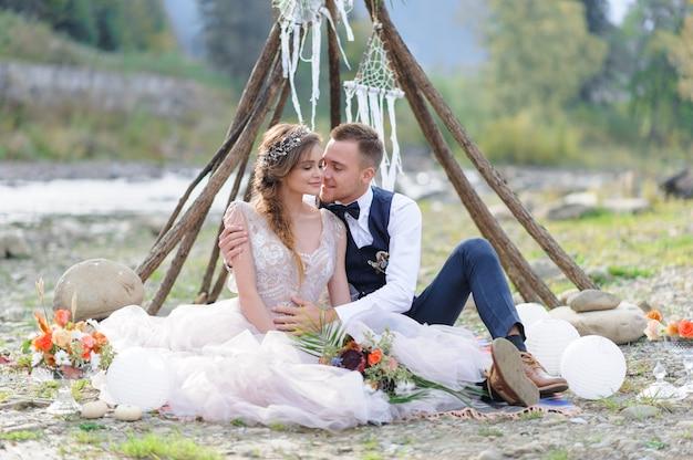 Man en vrouw knuffel en kus in vakantie kleding. man en vrouw knuffel en kus in vakantie kleding. bruiloft cermonia aan de rivier in de frisse lucht.