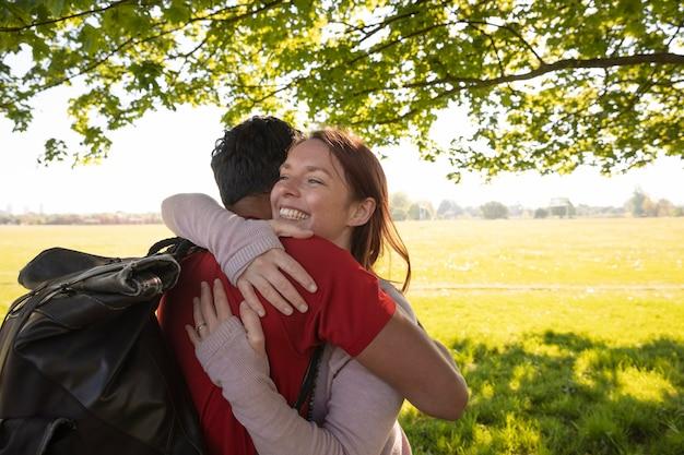 Man en vrouw knuffelen elkaar voordat ze buiten yoga doen