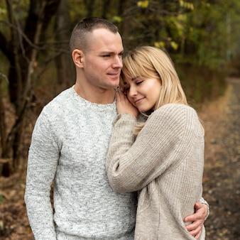 Man en vrouw knuffelen in de natuur
