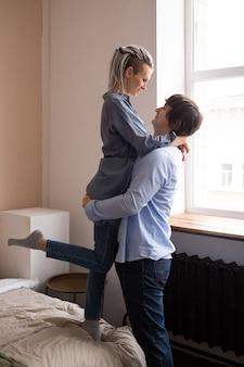 Man en vrouw knuffelen in de slaapkamer en kussen, liefde en relaties concept. valentijnsdag vieren.