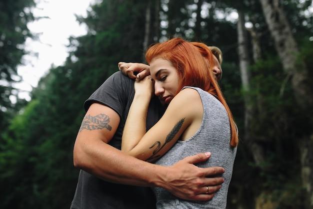 Man en vrouw knuffelen teder in de natuur