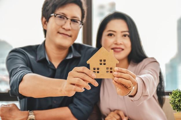 Man en vrouw kopen een huis, close-up hand met thuismodel
