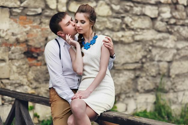 Man en vrouw kussen elkaar teder zittend op houten leuningen