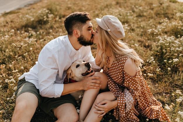 Man en vrouw kussen in park. paar genieten van geweldige dag zittend op het gras met hun labrador.