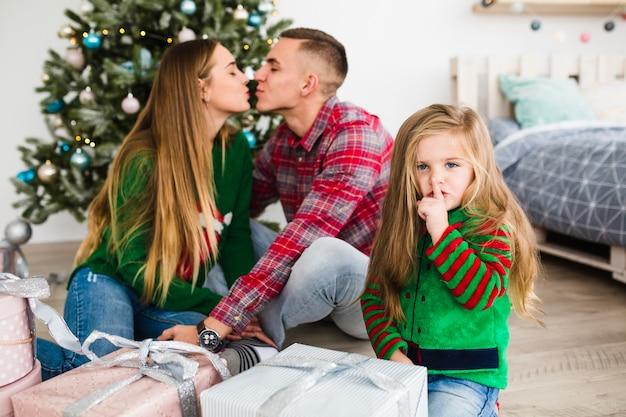 Man en vrouw kussen voor kerstboom