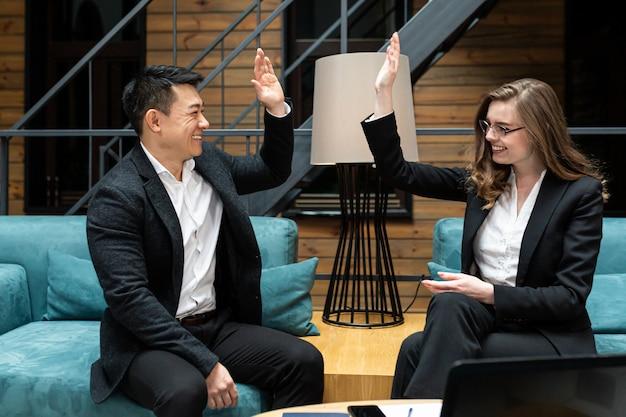 Man en vrouw lachende collega's vieren zakelijke overwinning Premium Foto