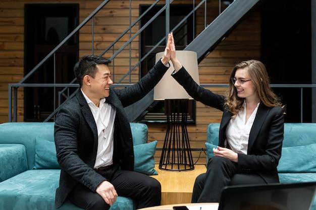 Man en vrouw lachende collega's vieren zakelijke overwinning