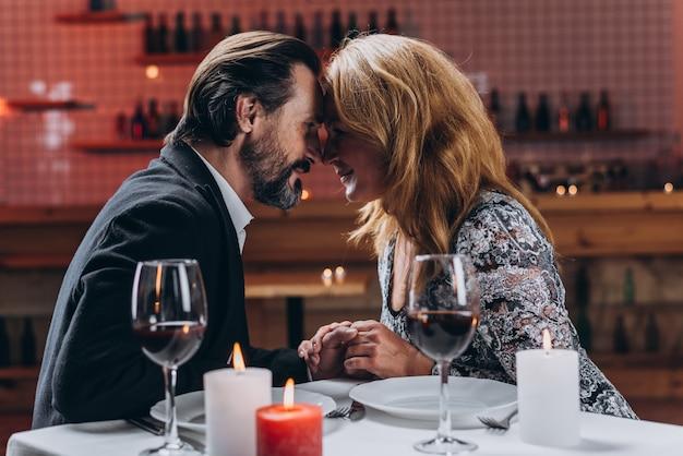 Man en vrouw leunden tegen elkaar hand in hand in een restaurant