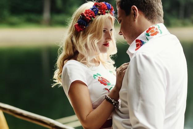Man en vrouw leunen tegen elkaar koppen die op houten veranda over bergmeer staan