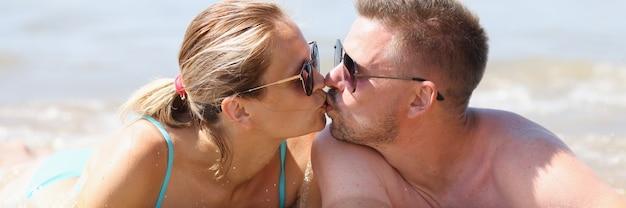Man en vrouw liggen op het strand en kussen