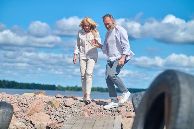 Man en vrouw lopen op stenen in de buurt van zee
