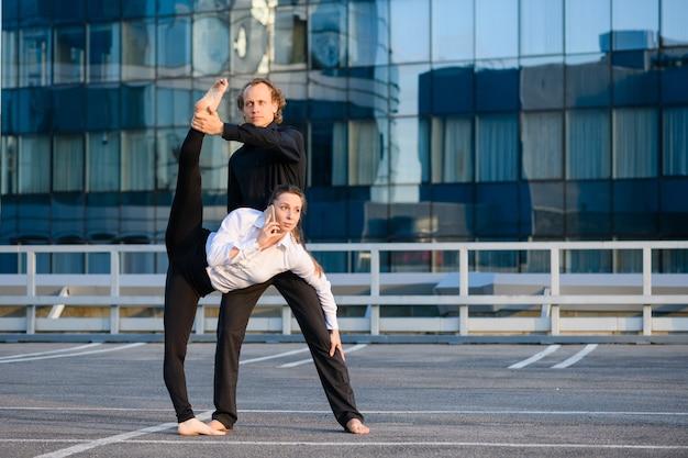 Man en vrouw maken acroyoga-element met vrouwelijk been omhoog, ze praat via de telefoon, zaken en sportconcept op een moderne glazen bouwachtergrond