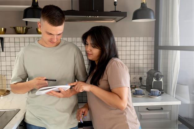 Man en vrouw maken samen boodschappenlijstje thuis in de keuken