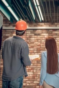 Man en vrouw mediteren voor bakstenen muur