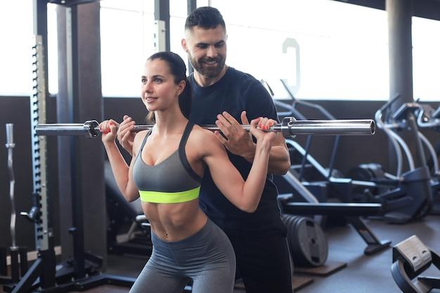 Man en vrouw met barbell buigen spieren in de sportschool.