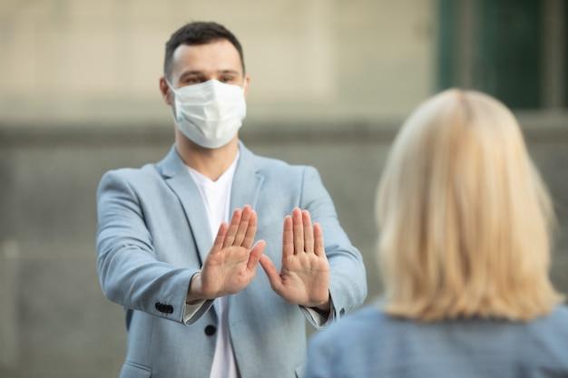 Man en vrouw met beschermende gezichtsmaskers die op 2 m van elkaar staan en sociale afstand houden om de verspreiding van het coronavirus te voorkomen