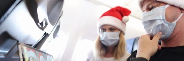 Man en vrouw met beschermende medische maskers en kerstmanhoeden vieren kerst met vrienden op...