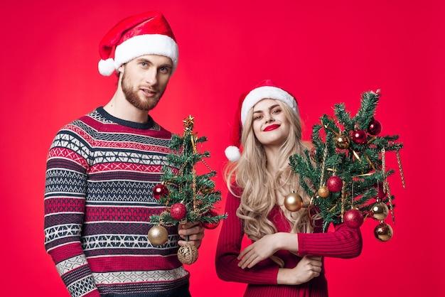 Man en vrouw met bomen in hun handen vakantie speelgoed decoratie rode achtergrond