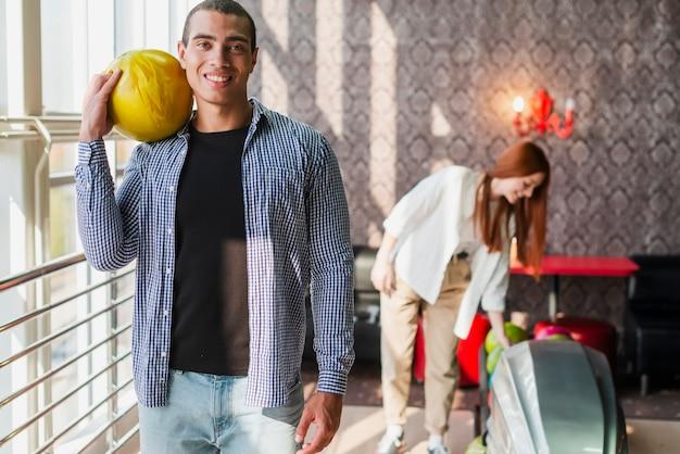 Man en vrouw met bowlingballen in een bowlingclub