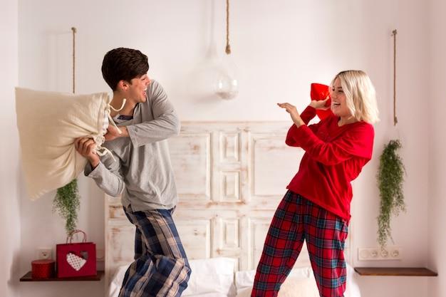Man en vrouw met een kussengevecht in de slaapkamer