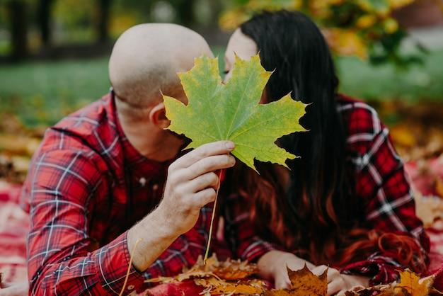 Man en vrouw met een plaid in herfstbladeren en bedekt met een esdoornblad