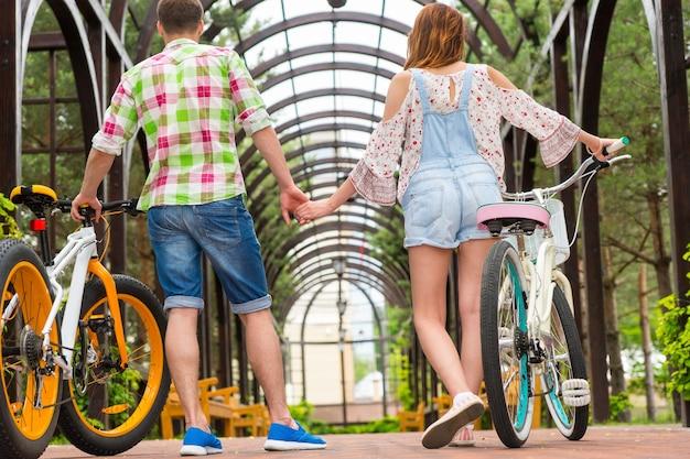 Man en vrouw met fietsen die elkaars hand vasthouden en hun vrije tijd doorbrengen in een boog in een park