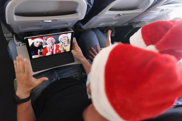 Man en vrouw met kerstmutsen wensen vrienden een gelukkig nieuwjaar en vrolijk kerstfeest via digitale tab...