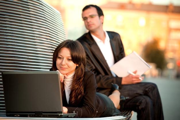 Man en vrouw met laptop en zittend op de bank voor kantoorgebouw bij zonnig weer