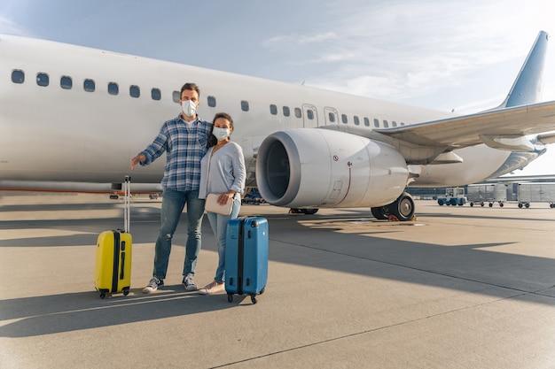 Man en vrouw met reistassen die in de buurt van vliegtuig staan