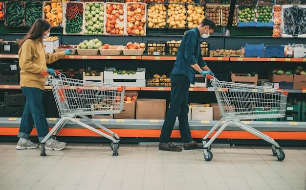 Man en vrouw met winkelwagentjes in een supermarkt tijdens de quarantaineperiode. foto met een kopie-ruimte