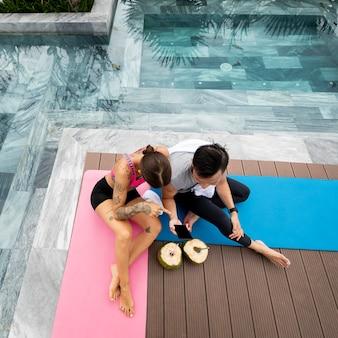 Man en vrouw nemen foto van kokosnoten na yogasessie