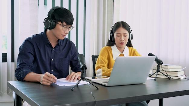 Man en vrouw nemen samen een podcast op of interviewen elkaar voor radio in de studio.