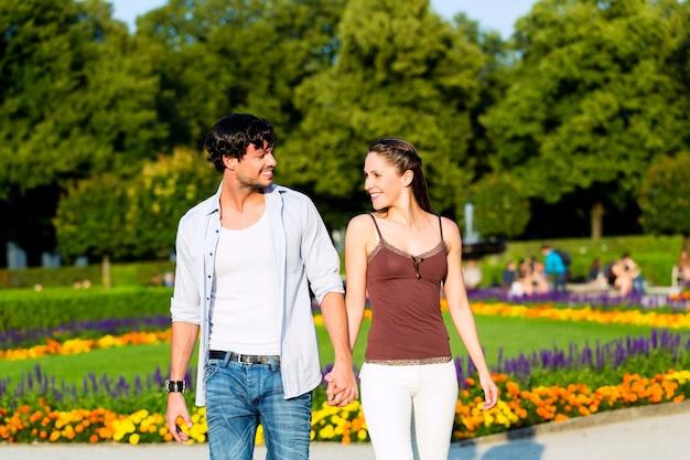 Man en vrouw of jong stel die een reis maken als toeristen in park die hand in hand lopen