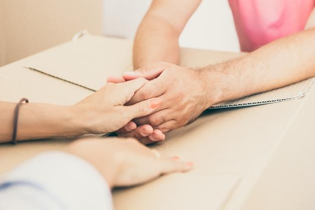 Man en vrouw ondersteunen elkaar en houden elkaars hand vast over kartonnen verpakking, terwijl ze naar een nieuw appartement verhuizen.