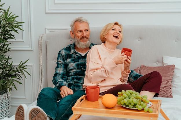 Man en vrouw ontbijten op bed met koffie en fruit