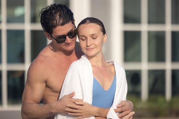 Man en vrouw ontspannen op het dek van het overloopzwembad in zwemkleding