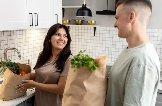 Man en vrouw ontvangen papieren boodschappentassen na online winkelen