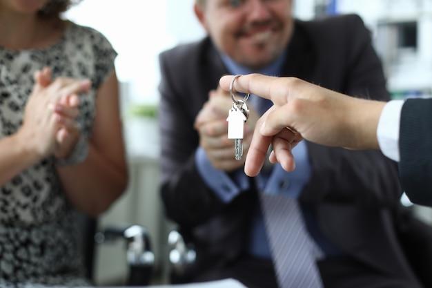 Man en vrouw ontvangen sleutel tot appartement van verkoper in kantoor close-up