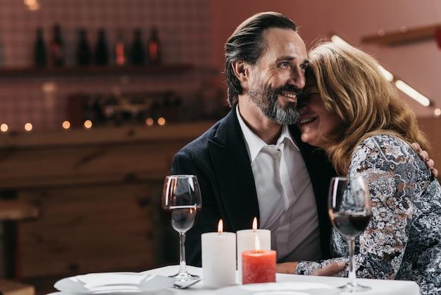 Man en vrouw op middelbare leeftijd die tegen elkaar bij een lijst in een restaurant leunen