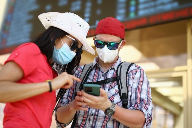 Man en vrouw op treinstation in beschermende medische maskers onderzoeken smartphon