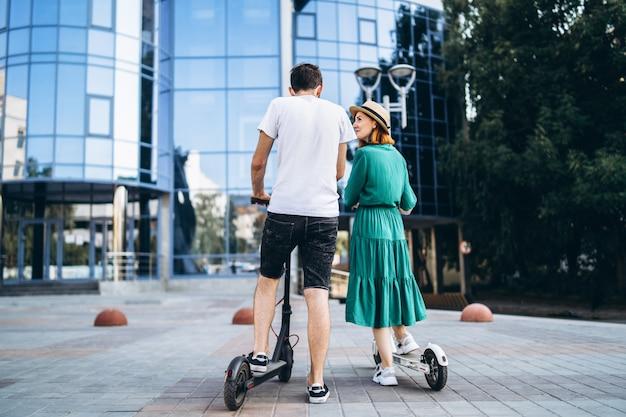 Man en vrouw op zwart-witte elektrische autopedden. achteraanzicht inhoudstechnologieën