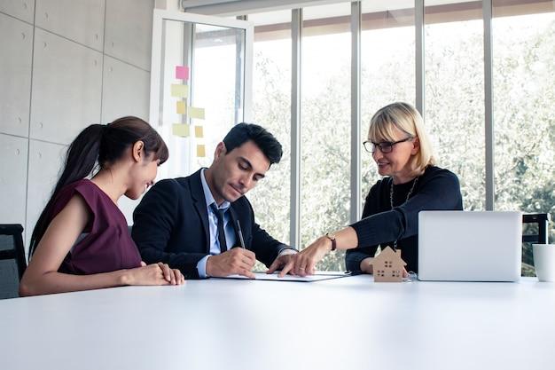 Man en vrouw overleggen met de eigenaar over het koopcontract.