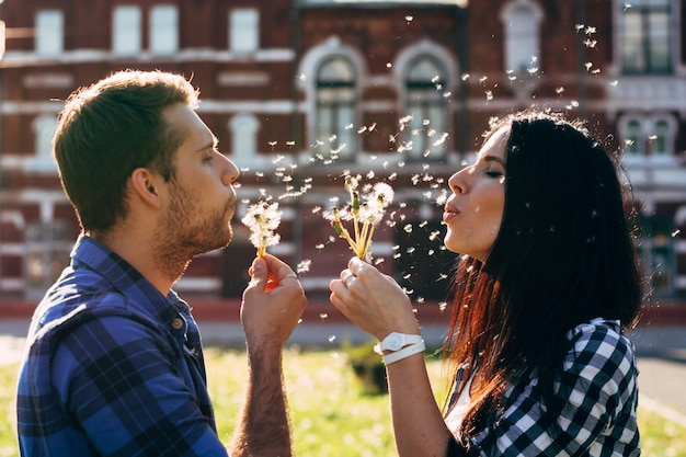 Man en vrouw paardebloemen blazen op elkaar