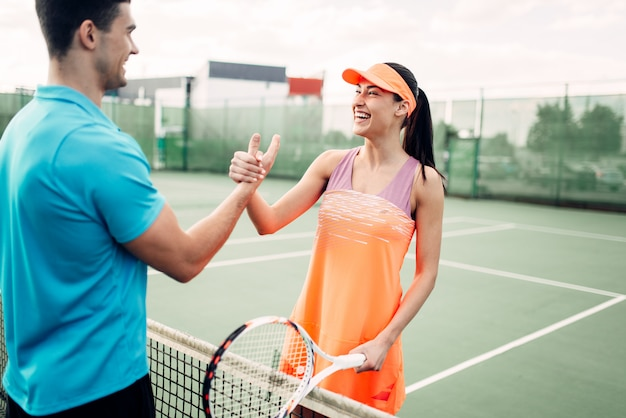 Man en vrouw partners op outdoor tennisbaan. zomerseizoen actief sportspel