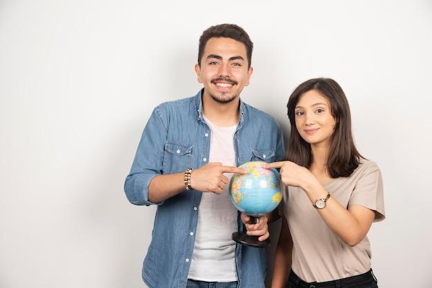 Man en vrouw poseren met globe op wit.