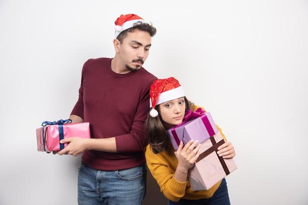 Man en vrouw poseren met kerstcadeautjes.