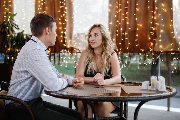 Man en vrouw praten aan een tafel in een café